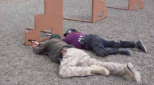 The author and an instructor at Thunder Ranch shoot around low cover from a prone position as part of a defensive training program. (Photo by Tom Walls)